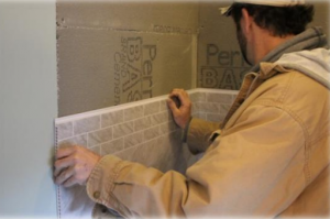An installer works with Bella Core Grout-Free Vertical Surfaces